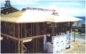 "[16 and  17 August: This photo and the previous one were taken a day apart, at the end of each  work day, and show the start and completion of roof sheathing installation.  The photo also shows the shingles loaded on the roof and the start of the vapor barrier ""wrapping"".]"