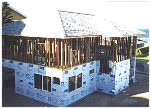 [18 August: The first floor has been moisture barrier wrapped and windows installed.]
